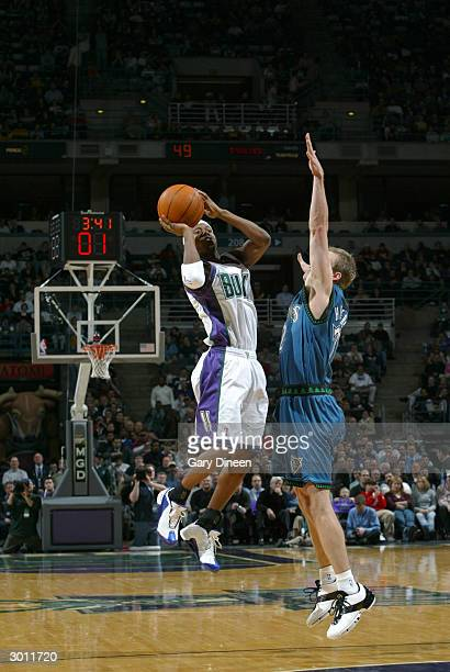 J Ford of the Milwaukee Bucks tries to beat the shot clock and a defending Trenton Hassell of the Minnesota Timberwolves on February 24 2004 at the...