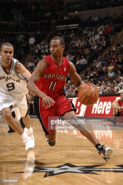 Ford of the Toronto Raptors dribbles the ball while Tony Parker of the San Antonio Spurs guards him during the game at the AT&T Center February 26,...