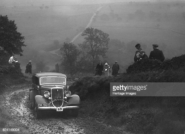 Ford V8 saloon of WT Platt competing in the MCC Sporting Trial 1935 Artist Bill BrunellFord V8 Saloon 1934 3622 cc Vehicle Reg No DK9615 Event Entry...