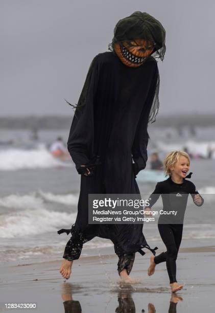 "Ford Waite is chased by an 8-foot-tall Jack-o""u2019-Lantern, Dave Wagner during Blackies 17th Annual Halloween Surf event on Saturday, October 31,..."