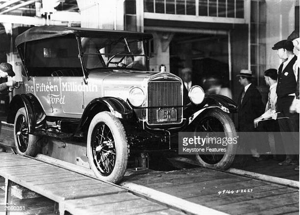 A Ford worker adds the final touches to the fifteenth million Ford car produced a Model T Ford in the USA