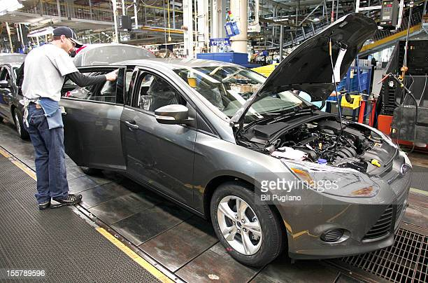 Ford worker assembles a 2013 Ford Focus gasolinepowered vehicle at the Michigan Assembly Plant November 8 2012 in Wayne Michigan The plant is the...
