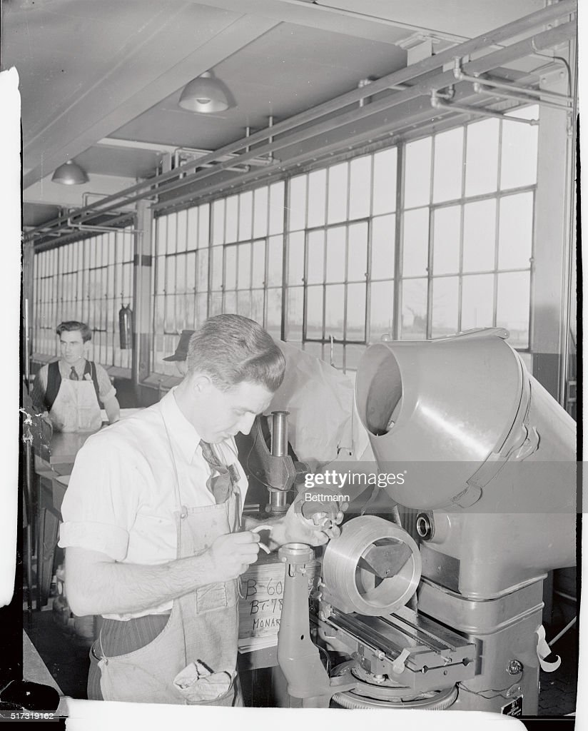 A Ford workman holds parts of a shadowgraph machine used for