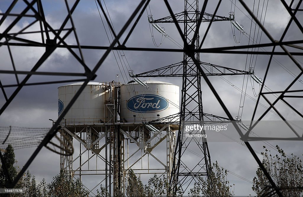 Ford-branded water towers stand near electricity pylons at the Ford Motor Co. automobile plant in Dagenham, U.K., on Monday, Oct. 29, 2012. Ford Motor Co. will shut three European plants, its first factory closings in the region in a decade, and cut 5,700 jobs to stem losses that the carmaker predicts will total more than $3 billion over two years. Photographer: Simon Dawson/Bloomberg via Getty Images