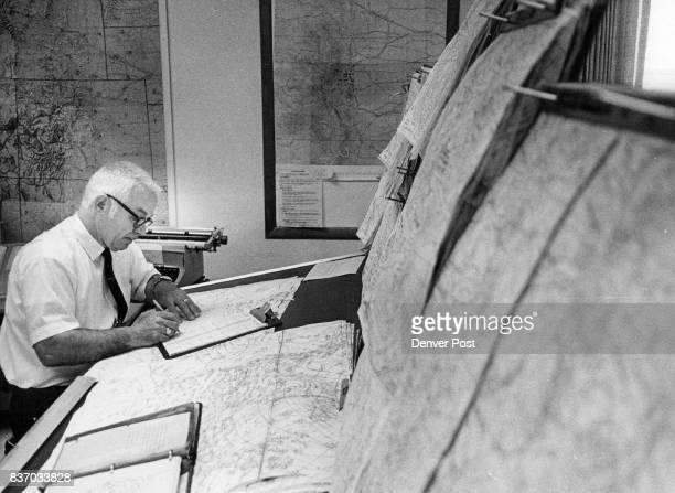 Forecaster Harry Emerson studies maps of air currents and fronts determined by the Denver office of the US Weather Bureau or received from other...