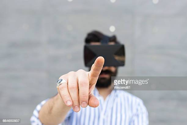 Forefinger of man playing with Virtual Reality Glasses typing in the air