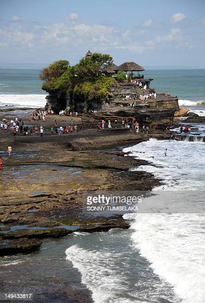 Foregin tourists look at Balinese people carrying offerings during Nyegara Gunung ceremony at Tanah Lot temple in Tabanan on Bali island on July 28,...