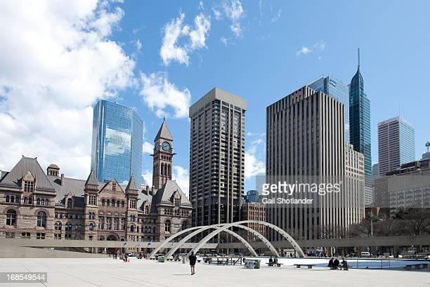 People site and walk on Toronto's Nathan Phillip's Square with rink / fountain Background Toronto's Old city Hall and other surrounding commerce...