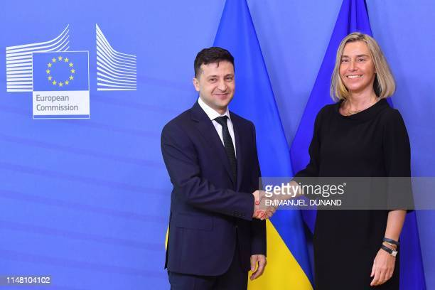 EU foreign affairs chief Federica Mogherini shakes hands with Ukraine's President Volodymyr Zelensky as he arrives at the European Commission in...