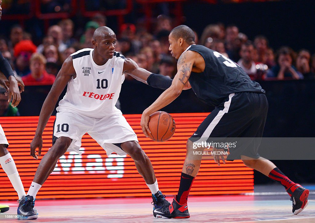 Foreign All Star player Bernard King (R) vies with French All star player Amara Sy (L) during France's national basketball league (LNB) 2010 All Star Game match on December 30, 2012 at the Palais Omnisport de Paris-Bercy (POPB) in Paris.