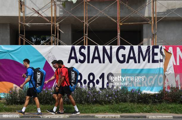 Foreign badminton athletes walk past labourers working on the old athletes villages renovation at the Senayan sports complex fortyseven days away...