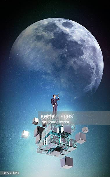 A foreign businessman looking at space through telescopes on top of moon and the cube