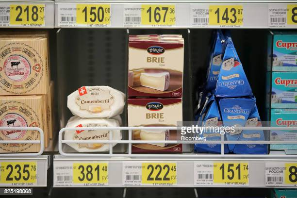 Foreign cheeses including brie and Moser Bio Camembertli from Switzerland sit on display at an Auchan Holding SA city supermarket operated by Groupe...