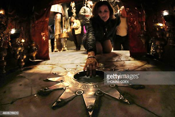 A foreign Christian worshiper touches the Bethlehem star inside the Grotto at the Church of the Nativity revered as the site of Jesus Christ's birth...