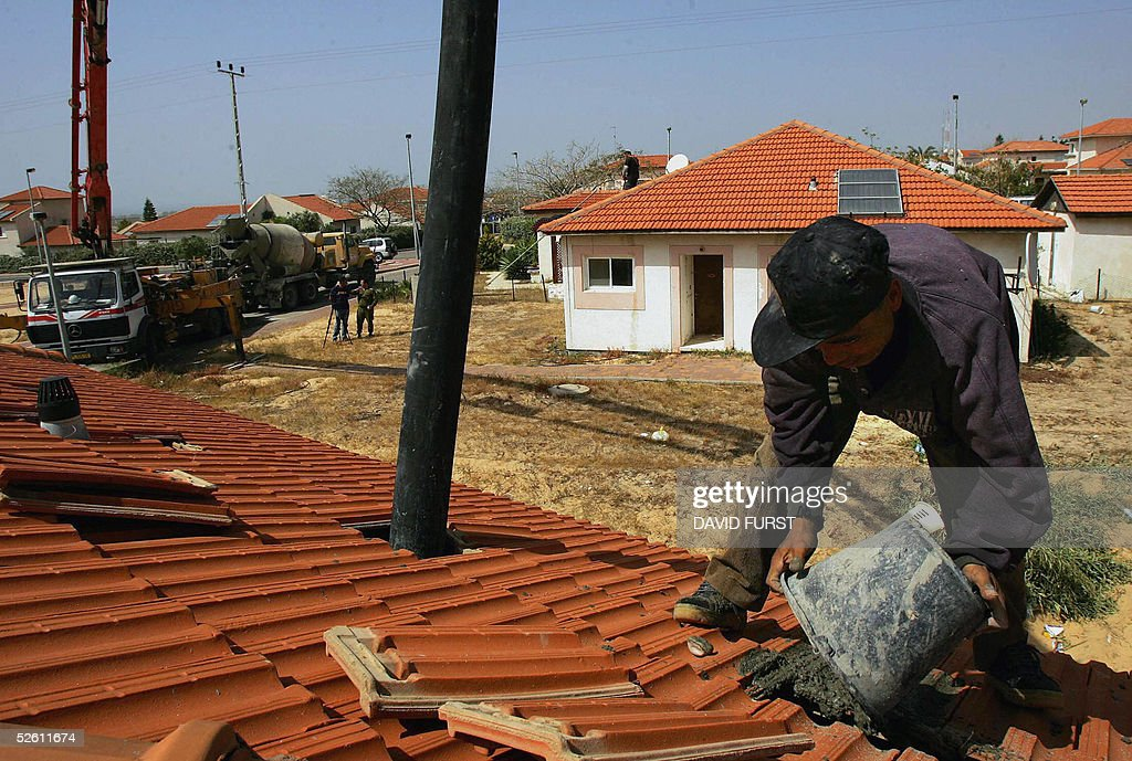 A foreign construction worker reinforces a roof with cement