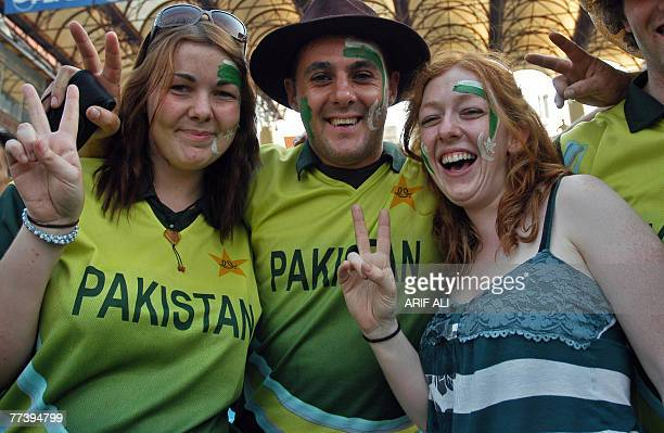 Foreign cricket fans wearing Pakistani team jerseys show victory signs during the first match of the One Day International series between Pakistan...