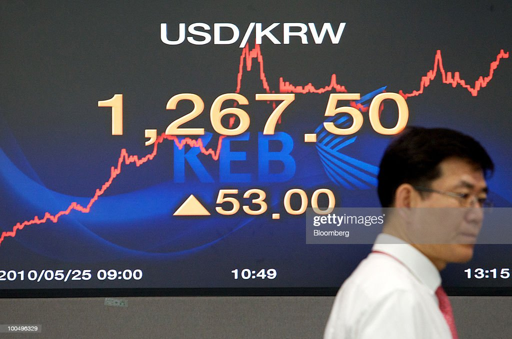 A foreign currency dealer walks past a monitor displaying the exchange rate between the U.S. dollar and the South Korean won at the headquarters of Korea Exchange Bank in Seoul, South Korea, on Tuesday, May 25, 2010. Asian stocks and the won plunged to 10-month lows after a report that North Korean leader Kim Jong Il ordered his military to prepare for combat last week. Photographer: SeongJoon Cho/Bloomberg via Getty Images