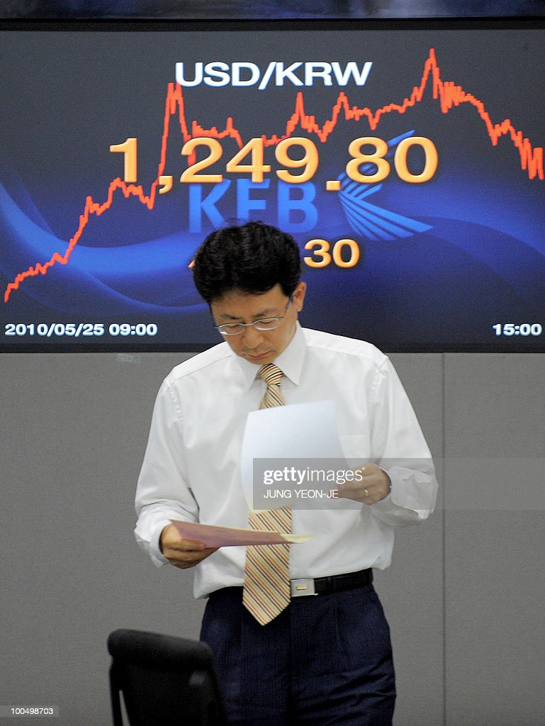 A foreign currency dealer walks past a screen showing the Korean won/USD exchange rate at the Korean Exchange Bank in Seoul on May 25, 2010. South Korea's currency and stock markets fell sharply amid escalating tensions over the deadly sinking of a warship and Europe's debt crisis.