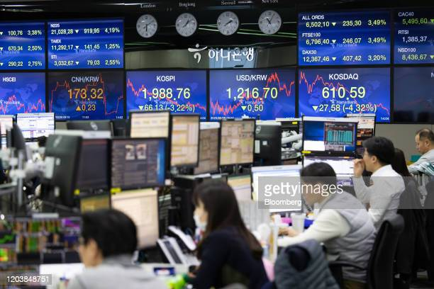 Foreign currency dealers work in a dealing room of Hana Bank in Seoul, South Korea, on Friday, Feb. 28, 2020. Fear tightened its grip on...