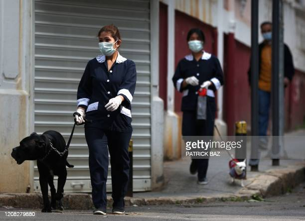 Foreign domestic workers wearing protective face masks walk their employees' dogs in the Lebanese capital Beirut on March 26 as most people remain at...