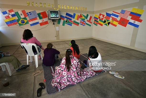 Foreign female inmates gather to watch television in a hall with flags from several countries at the Ancon 2 prison part of the Piedras Gordas Model...