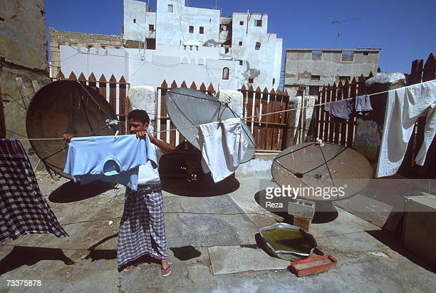 A foreign 'guest worker' from India hangs laundry on the rooftop of his apartment building on March 2003 in the immigrantcrowded historic district of...