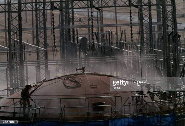 A foreign 'guest worker' wearing a protective suit sandblasts a storage tank at the Haradh Natural Gas And Oil Development Project part of a...