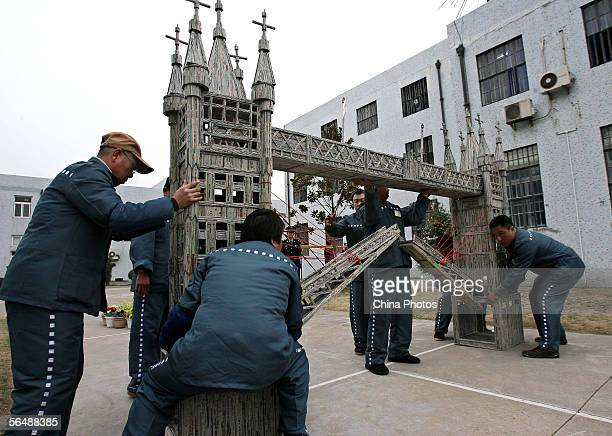 Foreign inmates try to remove a paper model of London Bridge made by them for a handcraft works exhibition held to mark Christmas at the Shanghai...