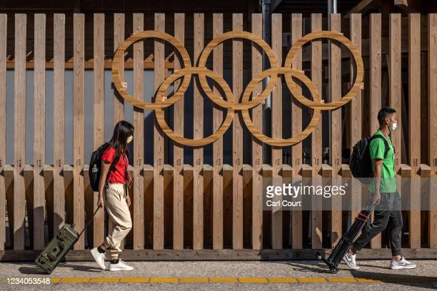 Foreign journalists carry broadcast equipment past Olympic Rings as they walk to the media centre at Tokyo Olympics athletes village on July 19, 2021...