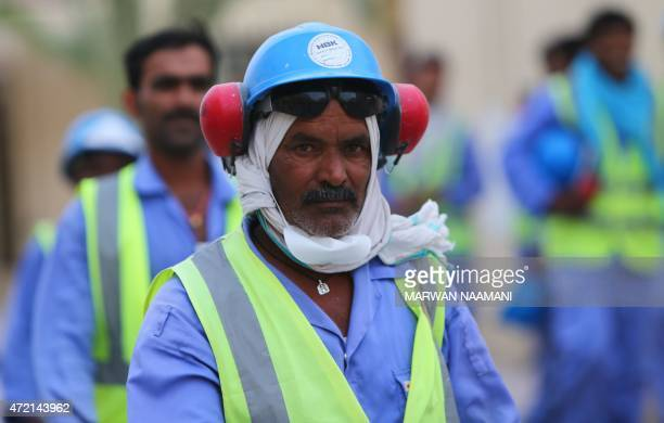 Foreign laborers working on the construction site of the alWakrah football stadium one of the Qatar's 2022 World Cup stadiums walk back to their...