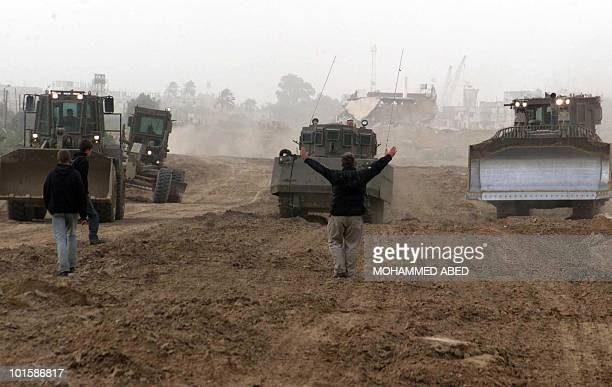 Foreign members of the International Solidarity Movement stand in front of Israeli armoured personnel carrier and bulldozers during a demonstration...