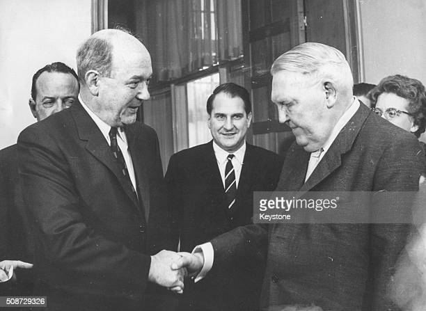 US Foreign Minister Dean Rusk shaking hands with new German Chancellor Ludwig Erhard watched by US ambassador to West Germany George C McGhee in Bonn...