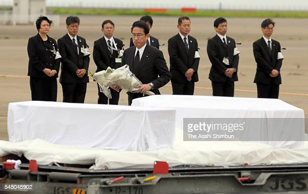 Foreign Minister Fumio Kishida places flowers on a coffin of Japanese victim of Dhaka terrorist attack at the Haneda Airport on July 5 2016 in Tokyo...