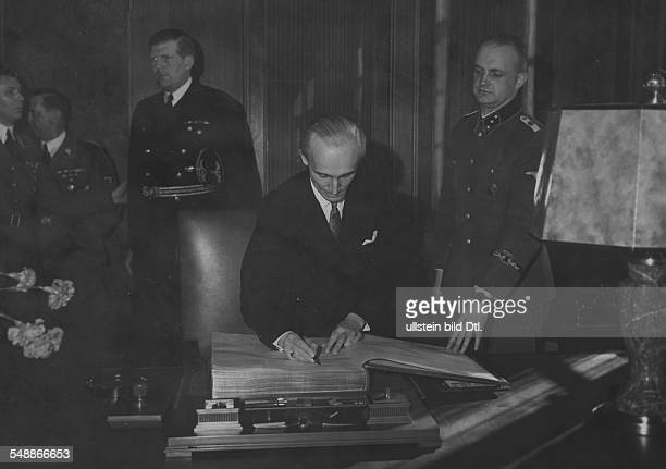 Foreign Minister Laszlo v Bardossy signing the guest book of the 'Fuehrerbau' at the Koeniglicher Platz in Munichin the background from left Hitler's...