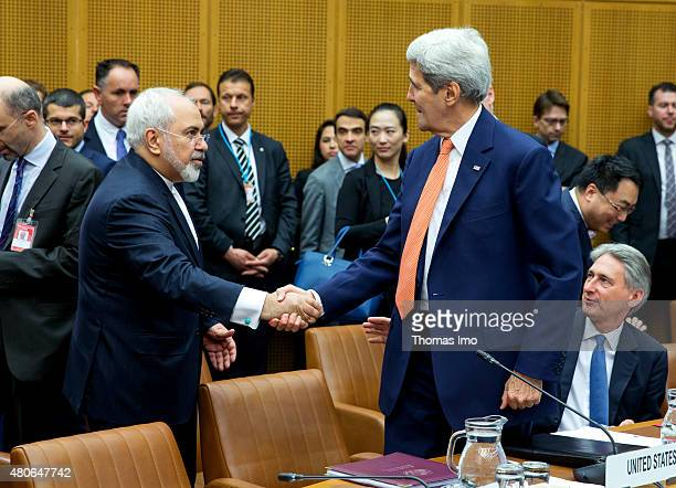 Foreign Minister of Iran Mohammad Javad Zarif shakes hands with US Secretary of State John Kerry at the last working session of E 33 negotiations on...
