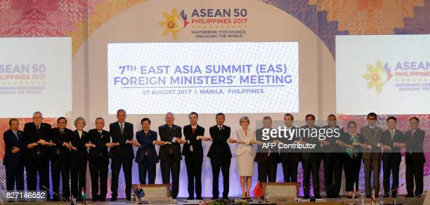 Foreign ministers from Southeast Asia and their dialogue partners link arms during the group photo at the start of the 7th East Asia Summit Foreign...