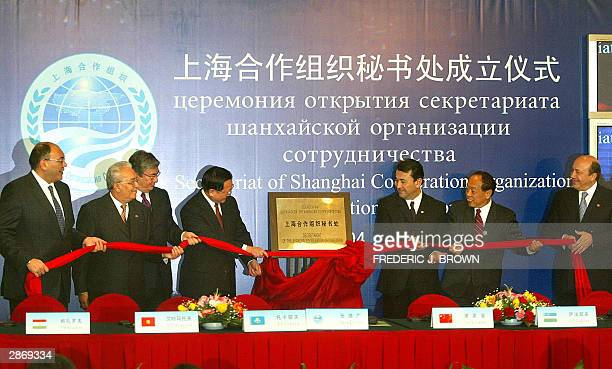 Foreign Ministers representing the sixnation Shanghai Cooperation Organisation including China's State Councillor Tang Jiaxuan unveil a commemorative...