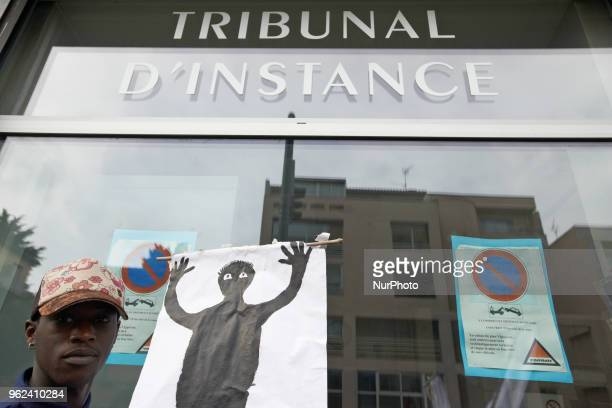 A foreign minor holds a drawing depicting himself at the entrance of the Small claims Court Unaccompanied foreign minors gathered in front of the...