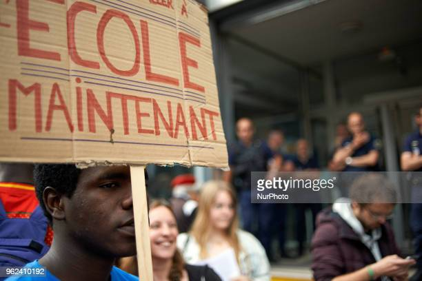 A foreign minor holds a placard reading 'School now ' Unaccompanied foreign minors gathered in front of the Small Claims Court in toulouse as the...