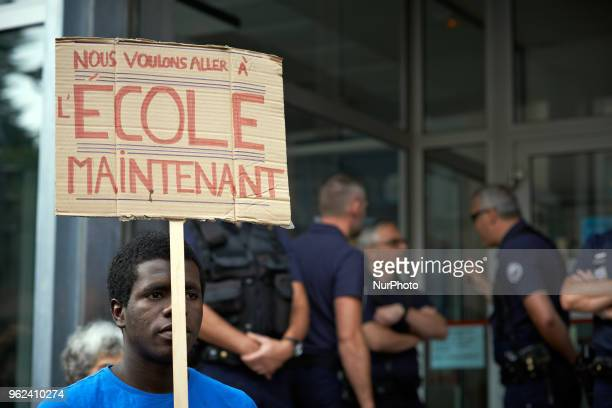 A foreign minor holds a placard reading 'We want to go to school now ' Unaccompanied foreign minors gathered in front of the Small Claims Court in...