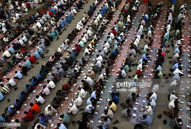 Foreign Muslim workers break their fast with a free Iftar dinner during the holy month of Ramadan in Dubai on July 15 2013 Muslims fasting in the...