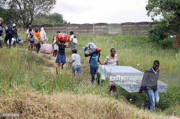 Foreign nationals carry their belongings before boarding a bus back to Zimbabwe from a temporary refugee camp in Chatsworth, south of Durban on April...