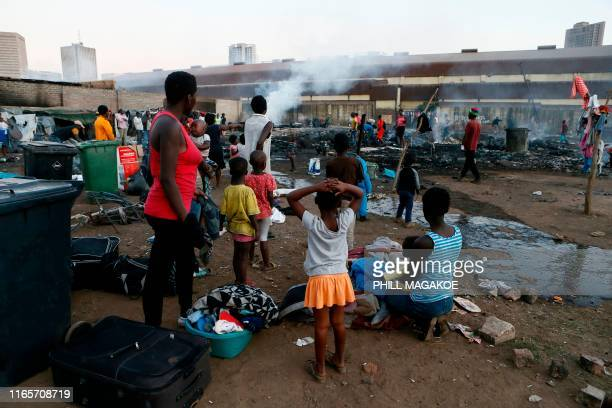TOPSHOT Foreign nationals sit and watch after their shacks were set alight by alleged looters at Marabastad near the Pretoria Central Business...