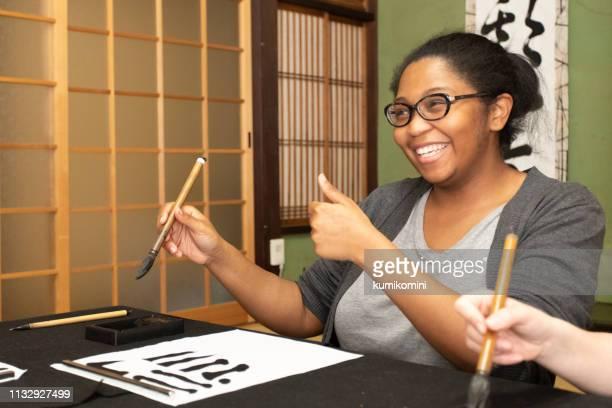 日本の書道を学ぶ外国人 - 日本語の文字 ストックフォトと画像
