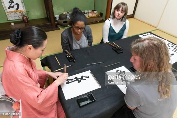 日本の書道を学ぶ外国人 - 書道 ストックフォトと画像