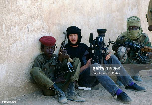 A foreign photojournalist rests next to a young rebel soldier with the Forces Armées Nationales Chadiennes or National Army of Chad after fighting...