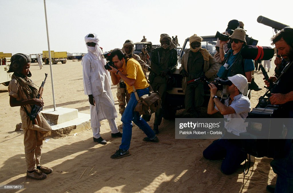 Foreign photojournalists covering the Chad Civil War photograph a child soldier with the Forces Armees Nationales Chadiennes (FANT), or National Army of Chad, holding an assault rifle along the road on route to Wadi Doum. Their mission in early 1987 was to reconquer the Borkou-Ennedi-Tibesti Prefecture and recover the territory in northern Chad that had been under Libyan control.   Location: Near Wadi Doum, Chad.