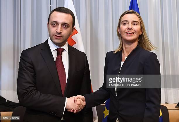 EU foreign policy chief Federica Mogherini mposes with Georgia's Prime Minister Irakli Garibashvili during the first EUGeorgia association council at...