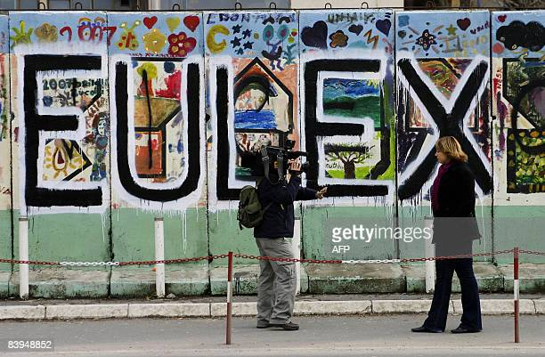Foreign reporters stand in front of grafiti reading EULEX in the Kosovar capital of Pristina on December 8 2008The EU agreed in February 2008 to send...