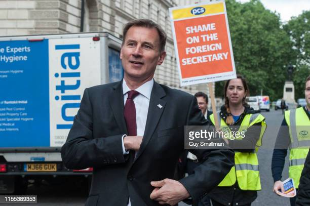Foreign secretary and Conservative leader candidate Jeremy Hunt walks past a picket line of striking cleaners outside his department he was given a...